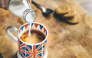 Milk being poured into a cup of tea in a mug decorated with a Union Jack flag